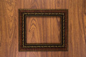 Gold frame on wood background  — Stock Photo
