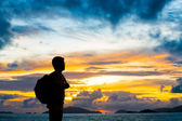 Silhouette traveler with backpack standing near the beach at sun — Stock Photo