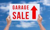 Two hands holding brown cardboard with garage sale on blue sky b — Stock Photo