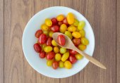 Red and yellow tomatoes with a spoon — Stock Photo