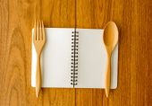 Blank notebook on plated with spoon and fork — Stock Photo