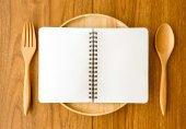 Puste notebooka na pokrytym łyżka i widelec — Zdjęcie stockowe