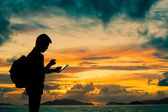 Silhouette man with digital tablet in hands at sunset beach — Stock Photo