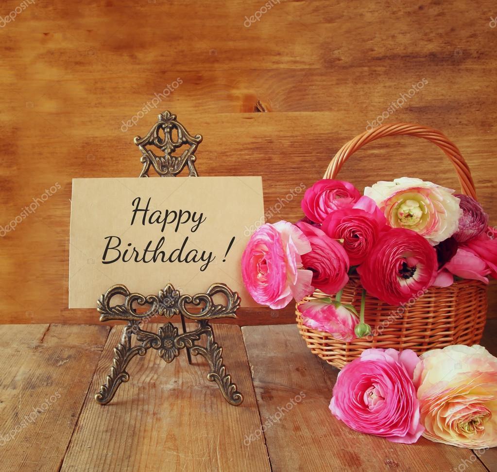 rosa flores en la cesta junto a la tarjeta con frase feliz cumplea os en mesa de madera. Black Bedroom Furniture Sets. Home Design Ideas