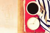 Top view of coffee cup, old clock book and blanket over wooden table. filtered image — Stok fotoğraf