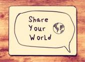 White board with the phrase share your world, over wooden textured background. — Stock Photo