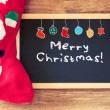 Red sock and blackboard with merry christams greeting and colorful icons. christmas card concept — Stock Photo #53386587