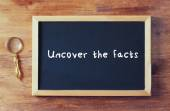 Top view of blackboard with the phrase uncover the facts written — ストック写真
