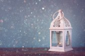 White lantern over wooden table and glitter lights background — Stock Photo