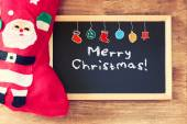 Red sock and blackboard with merry christams greeting and colorful icons. christmas card concept — Stock Photo