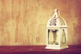 White lantern over wooden table. vintage effect — Stock Photo