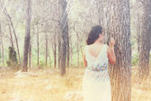 Surreal blurred background of young woman stands in forest — Stock Photo