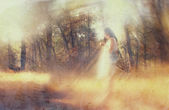 Surreal blurred background of young woman stands in forest. abstract and dreamy concept. image is textured and retro toned — Стоковое фото