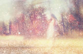 Surreal blurred background of young woman stands in forest. abstract and dreamy concept. image is textured and retro toned — Stock Photo
