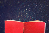 Open red book and glowing glittering lights — Stock Photo