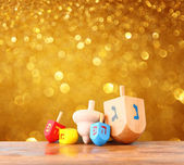 Wooden dreidels for hanukkah and glitter golden lights background — Stock Photo