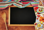 Top view of blackboard and wooden spoon over wooden table and collage of photos with various food and dishes — Stock Photo