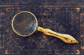 Macro image of magnifying glass over antique black cover — Foto de Stock