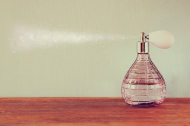 Vintage antigue perfume bottle with effect of perfume spray, on wooden table. retro filtered image
