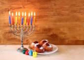 Jewish holiday Hanukkah with menorah, doughnuts and wooden dreidels (spinning top). — Stock Photo