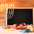 Jewish holiday Hanukkah with menorah, doughnuts over wooden table — Stock Photo #56372807