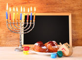 Jewish holiday Hanukkah with menorah, doughnuts over wooden table — Stock Photo