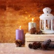 Vintage Lantern with burning candles, pine cones on wooden table and glitter lights background. filtered image — Stock Photo #56484307