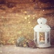 White vintage Lantern with burning candles, pine cones on wooden table and glitter lights background. filtered image — Stock Photo #56513173