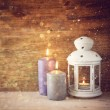 Vintage Lantern with burning candles on wooden table and glitter lights background. filtered image — Stock Photo #56513779