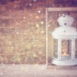 Vintage Lantern with burning candles on wooden table and glitter lights background. filtered image — Stock Photo #56513805