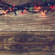 Colorful Christmas lights on wooden  rustic background. filtered image — Stock Photo #56515125