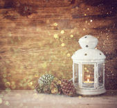 White vintage Lantern with burning candles, pine cones on wooden table and glitter lights background. filtered image — Foto de Stock