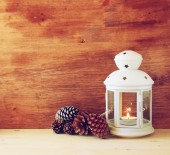 Vintage Lantern with burning Candle and pine cones on wooden table. filtered image — Stok fotoğraf