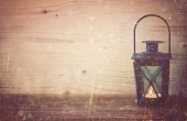 Vintage Lantern on wooden table and glitter lights background. filtered image — Foto de Stock