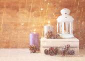 Vintage Lantern with burning candles, pine cones on wooden table and glitter lights background. filtered image — Foto de Stock