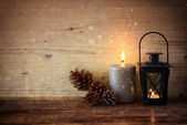 Vintage Lantern with burning candles, pine cones on wooden table and glitter lights background. filtered image — ストック写真