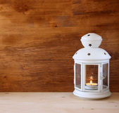 Vintage Lantern with burning Candle on wooden table. filtered image — Foto de Stock