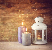 Vintage Lantern with burning candles on wooden table and glitter lights background. filtered image — Foto de Stock