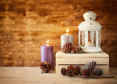 Vintage Lantern with burning Candle and pine cones on wooden table. filtered image — Foto de Stock