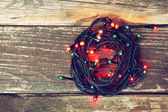 Colorful Christmas lights on wooden  rustic background. filtered image — Stock Photo