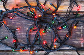 Colorful Christmas lights on wooden  rustic background. filtered image — 图库照片