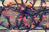 Colorful Christmas lights on wooden  rustic background. filtered image — Foto Stock