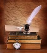 Lage belangrijke beeld van white Feather, inktpotje en oude boeken over oude houten tafel — Stockfoto