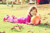 Little lovely girl playing with her ball on the grass in the park. filtered image — Stock Photo