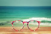 Glasses in front of sea landscape with open horizon. image is retro filtered. — Zdjęcie stockowe
