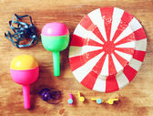 Top view of vintage party accessories - party hat maracas whistles and confetti over wooden board. — Foto de Stock