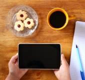 Vista superiore delle mani di donna che tengono dispositivo tablet con lo schermo vuoto, con biscotti e tazza di caffè. immagine è retrò filtrata — Foto Stock