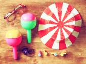 Top view of vintage party accessories - party hat maracas whistles and confetti over wooden board. — Stockfoto