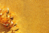Top view image of curly golden ribbon over textured glitter background — Zdjęcie stockowe