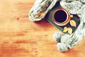 Top view of Cup of black coffee with autumn leaves, a warm scarf and old book on wooden background. filreted image — Stock Photo